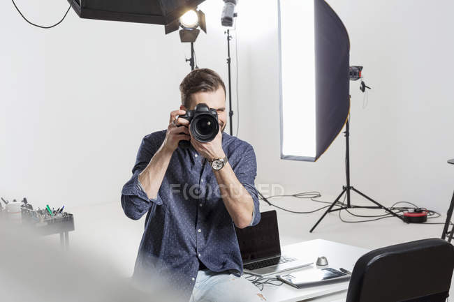 Male photographer testing focus on digital SLR in photography studio — Foto stock