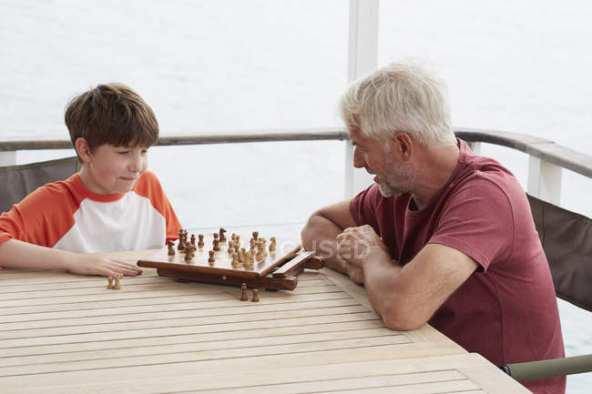 Grandfather and grandson playing chess together — Stock Photo