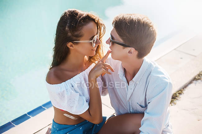 Young woman with finger on boyfriend's lips at poolside, Koh Samui, Thailand — Stock Photo