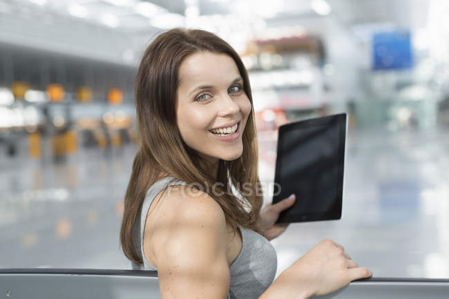 Portrait of businesswoman holding digital tablet looking over her shoulder in airport departure lounge — Stock Photo