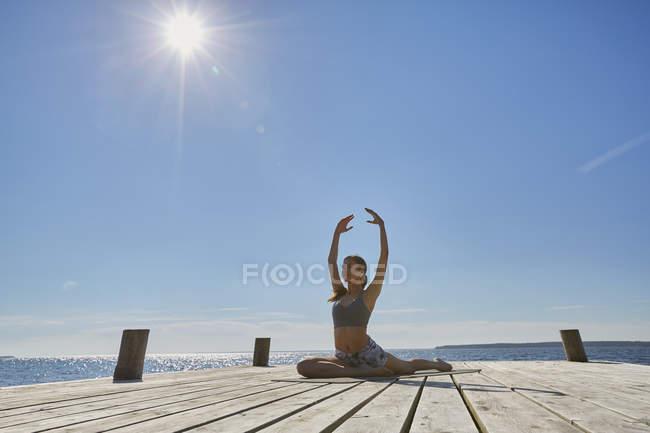 Mujer en muelle haciendo las fracturas de brazos levantados en posición de yoga - foto de stock