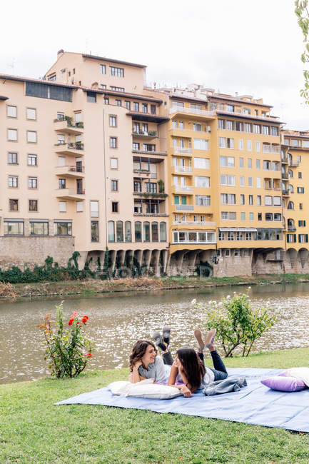Lesbian couple lying on front on blanket next to Arno river, Florence, Tuscany, Italy — Stock Photo