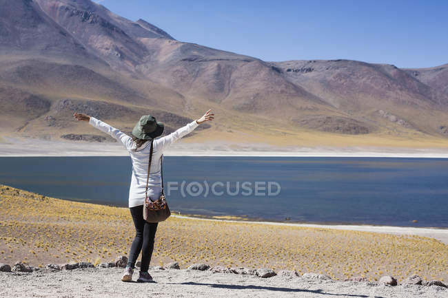 Back view of tourist woman with hands up at lake in San Pedro de Atacama, Chile — Stock Photo