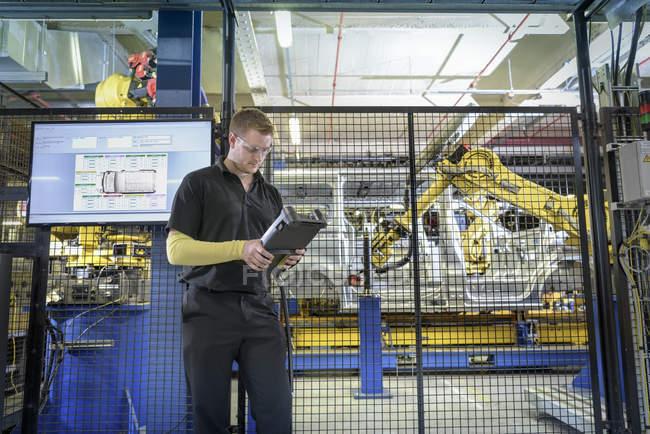 Ученик инженера, работающего роботами на производственной линии на автозаводе — стоковое фото
