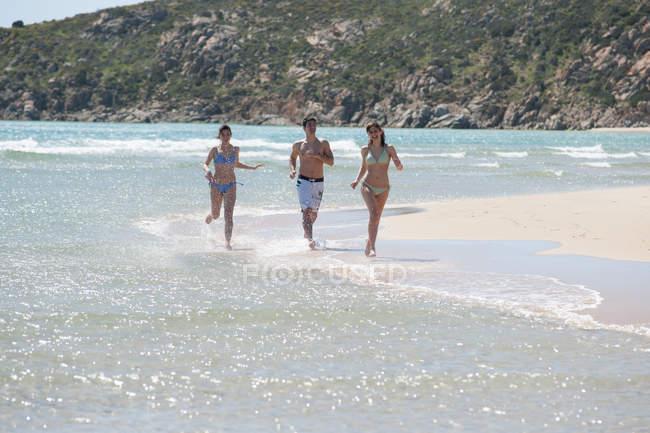 Друзі біг в хвилях на пляжі — стокове фото