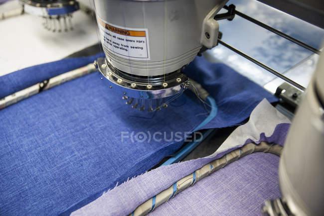 Programar a velocidade de máquinas de bordado costura pano azul e roxo em fábrica de roupas — Fotografia de Stock