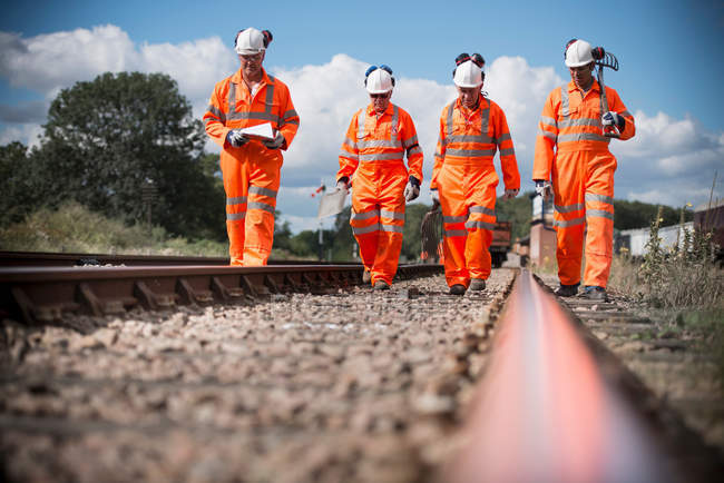 Railway workers walking down and checking tracks, front view — Stock Photo