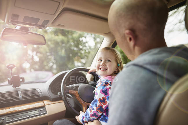 Over shoulder view of daughter sitting on father lap driving car — Stock Photo