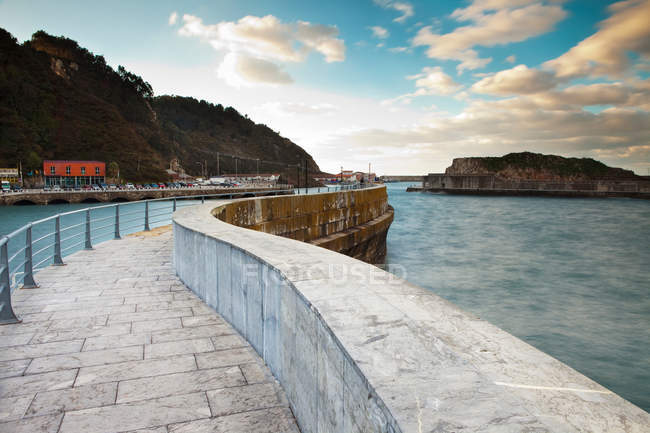 Ornate stone walkway at harbor under cloudy sky — Stock Photo