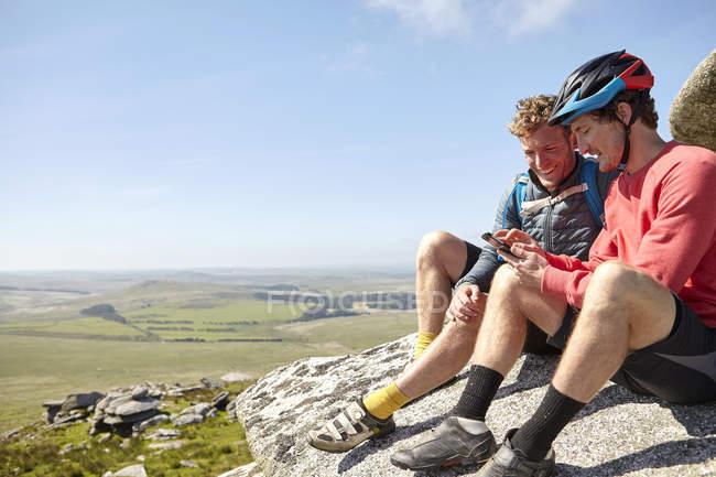 Ciclisti che riposa su sperone roccioso — Foto stock