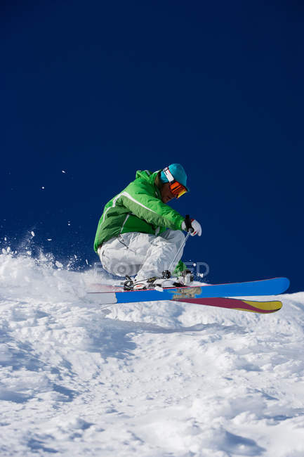 Man in green carving downhill. — Stock Photo