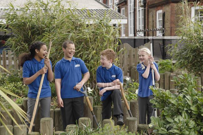 Grupo de quatro crianças da escola com ferramentas de jardinagem — Fotografia de Stock