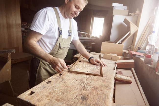 Vue latérale du charpentier d'homme dans le tablier travaillant avec des planches en bois — Photo de stock