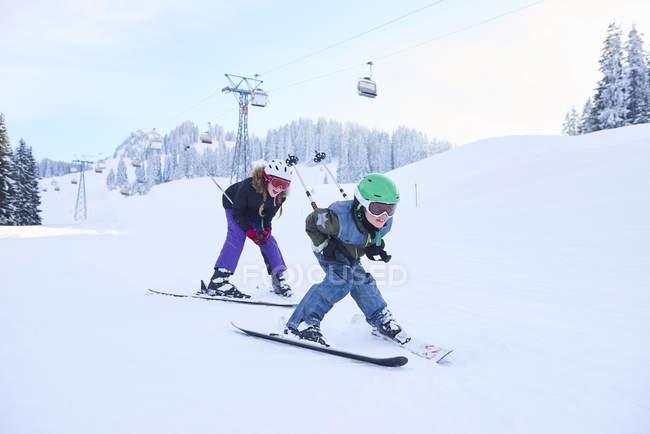 Девочка-подросток и брат катаются на лыжах по горнолыжному склону, Гштаад, Швейцария — стоковое фото