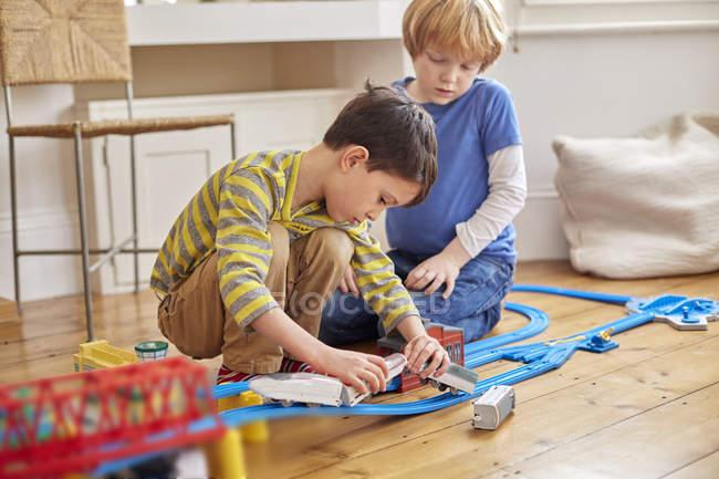 Двоє молодих хлопчиків грають з іграшкового поїзда набір — стокове фото