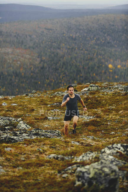 Man trail running on rocky cliff top, Keimiotunturi, Lapponia, Finlandia — Foto stock