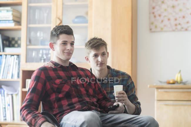 Joven usando silla de ruedas viendo televisión con un amigo en la cocina - foto de stock
