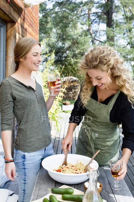 Dos amigos preparando almuerzo al aire libre - foto de stock