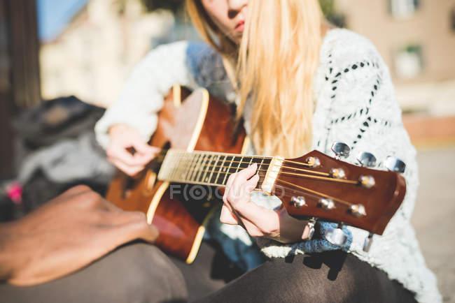 Frau spielt draußen auf der Straße Gitarre — Stockfoto