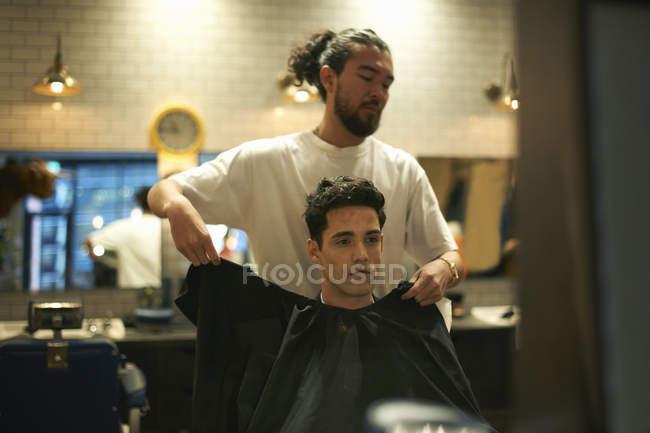 Перукарня покласти плаття на чоловічий клієнта в перукарні — стокове фото