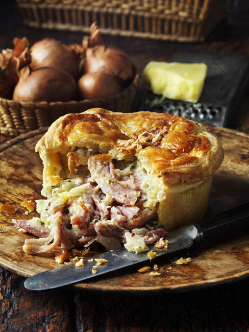 Ham cheese and onion pie with knife on plate u2014 Stock Photo & Ham cheese and onion pie with knife on plate u2014 Stock Photo | #168147300
