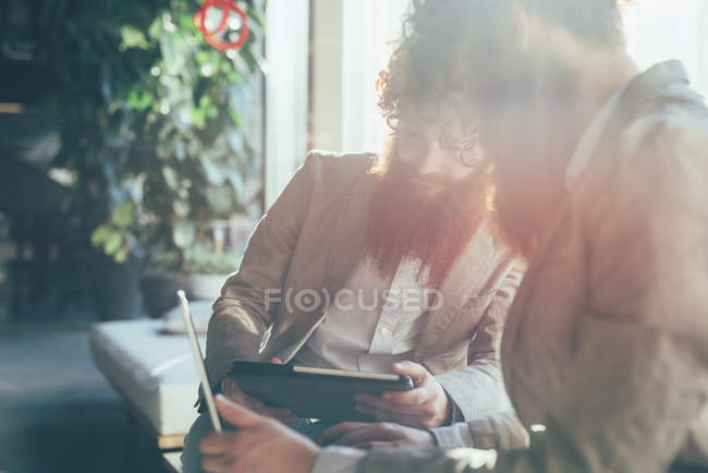 Male adult hipster twins working on digital tablet and laptop in office — Stock Photo