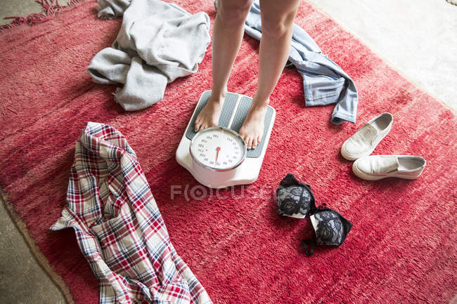 Legs of undressed young woman standing on weighing scales — Stock Photo