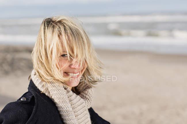 Donna sorridente in piedi sulla spiaggia — Foto stock