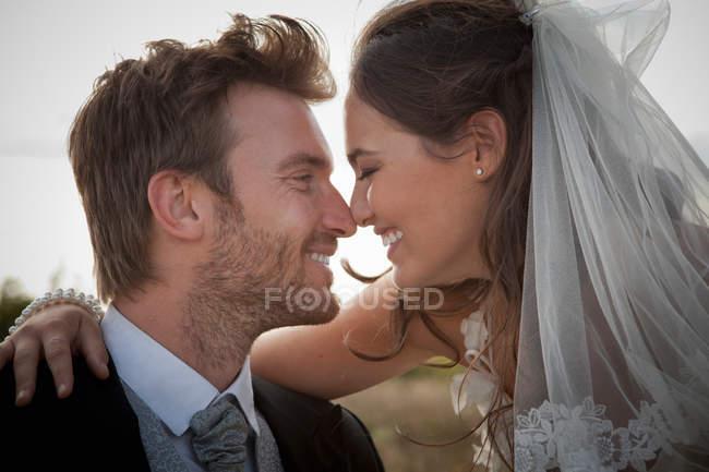Pareja de recién casados tocando las narices - foto de stock