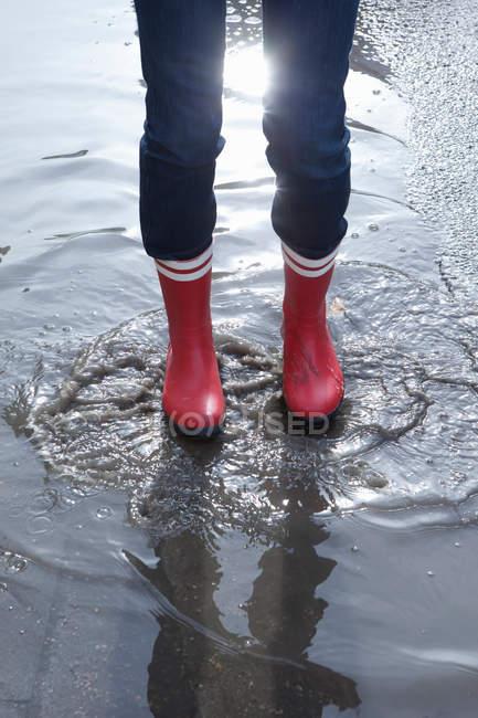Celui qui le porte en caoutchouc, bottes debout dans la flaque d'eau — Photo de stock
