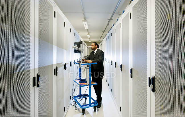 Businessman using computer with servers — Stock Photo