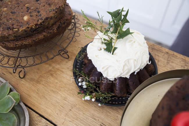 Pasteles en el mostrador de la cocina, uno decorado con glaseado y hojas - foto de stock
