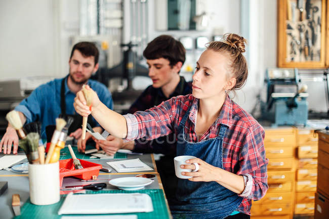 Молода Майстриня тримає чашку кави і простягаючи за кисть в творчій студії друку, з двома молодими майстрами, що працюють у фоновому режимі — стокове фото