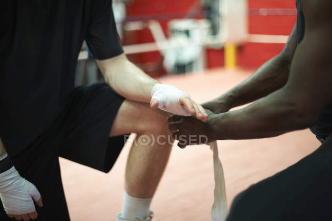 Coach helping boxer bandage hands before putting on gloves, mid section — Stock Photo
