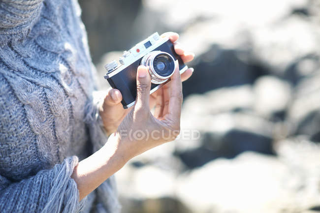 Woman adjusting aperture on film camera in sunlight — Stock Photo