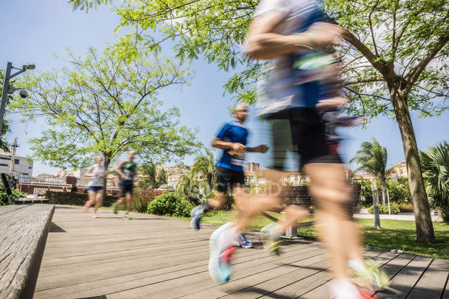 Blurred motion of runners running on park boardwalk — Stock Photo