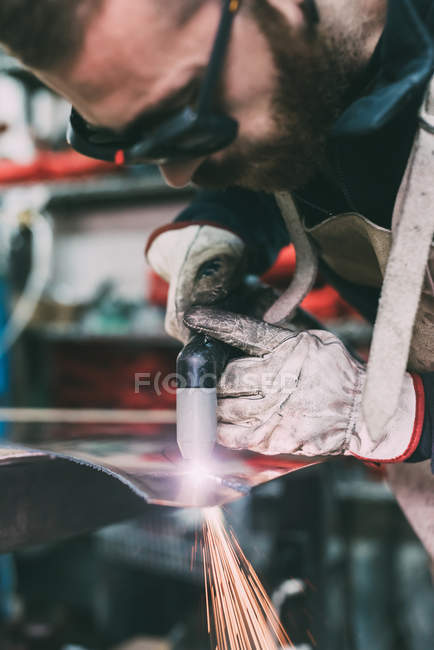 Metalworker plasma-cutting copper in forge workshop — Stock Photo