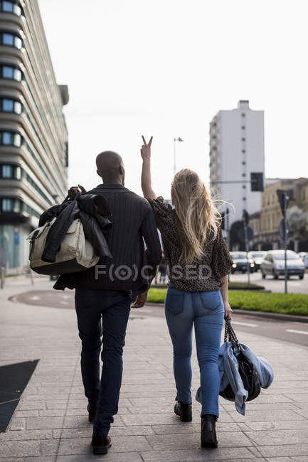 Back view of walking caucasian woman and African ethnicity man in street, couple in love carrying baggage, woman gesturing peace sign with fingers — Stock Photo