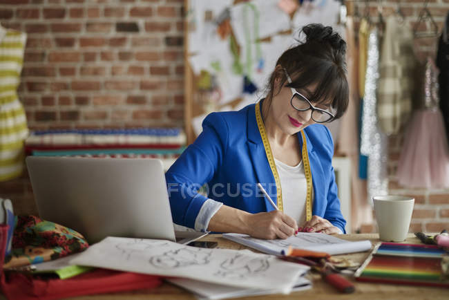 Woman in design studio sitting at desk sketching fashion design — Stock Photo
