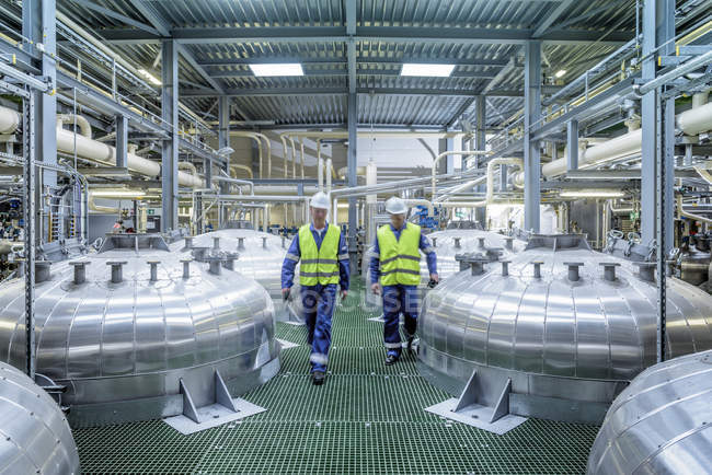 Workers with process machinery in oil blending factory — Stock Photo