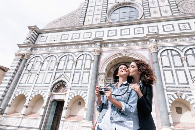 Low angle view of lesbian couple holding digital camera kissing on cheek in front of church, Piazza Santa Maria Novella, Florence, Tuscany, Italy — Stock Photo