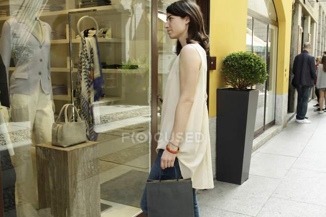Женщина в витрине бутика, Милан, Италия — стоковое фото