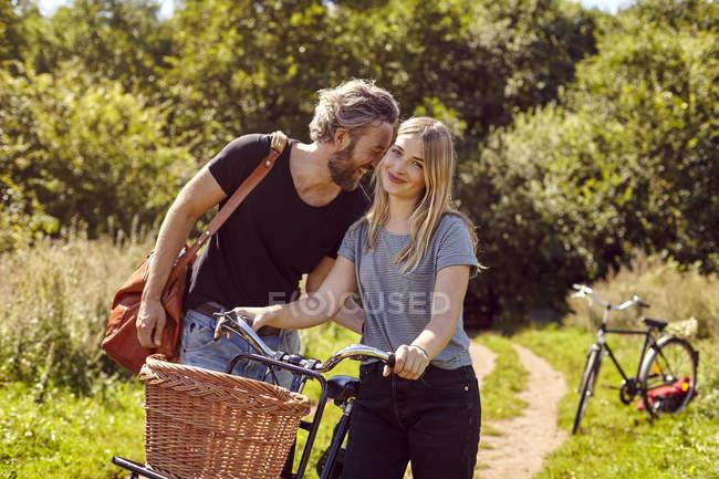 Портрет пары с велосипедами, смеющейся на сельской грунтовой дорожке — стоковое фото