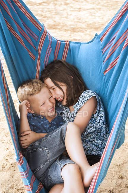 Дівчина і брат сміятися в той час як тулилися в гамаку — стокове фото