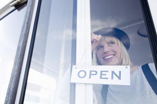 Жінка розміщення відкритим знаком на скляні двері посміхаючись — стокове фото