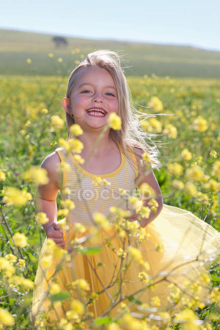 Smiling girl playing in field of flowers — Stock Photo