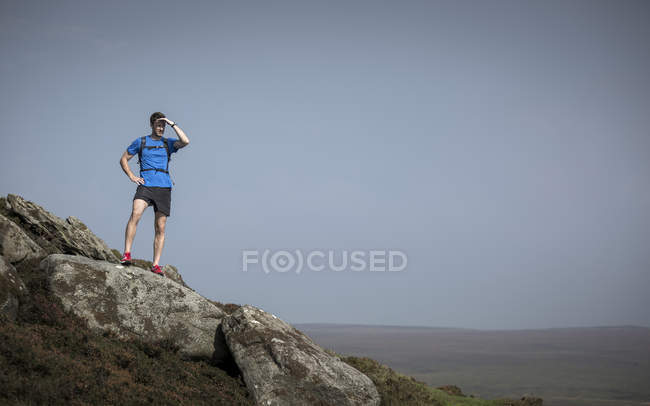 Male runner looking out from Stanage Edge, Peak District, Derbyshire, UK — Stock Photo