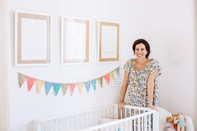 Portrait of pregnant mid adult woman leaning against crib in childs nursery — Stock Photo