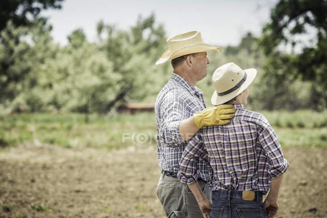 Agriculteur et petit-fils adolescent à l'affût de champ labouré — Photo de stock