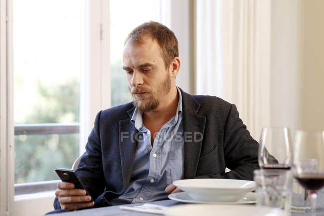 Hombre sentado en la mesa, usando smartphone - foto de stock
